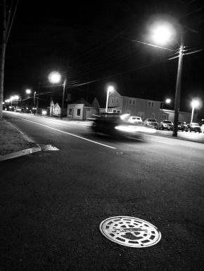 car passing night nighttime black and white lights motion blur dark streetlights street line